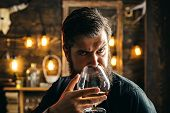 Man With Beard In Black With Glass Of Beverage. Bearded Man Holds Glass Of Brandy. Bearded Hipster D poster