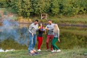 Picnic With Friends In At Lake Near Bonfire. Company Friends Having Hike Picnic Nature Background. H poster
