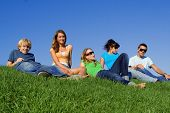 stock photo of summer fun  - group of happy teens relaxing laying on grass in summer - JPG