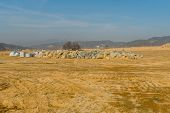 Grove Of Trees Behind Pile Of Large Landscaping Boulders And Concrete Blocks At Construction Site. poster