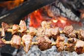 Pork Pieces On Wooden Stick (Traditional  Shish Kebab) Roasting Beside Open Fire poster