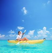 A young female in a yellow kayak kayaking near a Kuredu island, Maldives, Lhaviyani atoll