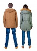 Back view of couple in winter jacket. beautiful friendly girl and guy together. Rear view people col poster