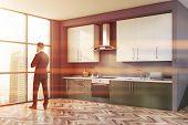 Thoughtful Businessman Standing In Stylish Sunlit Kitchen With Gray Walls, Wooden Floor, Green Count poster