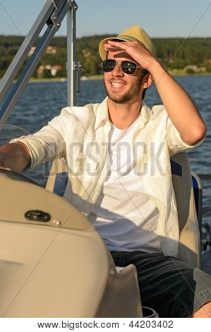 Man in sunglasses and straw hat navigating boat sunny day