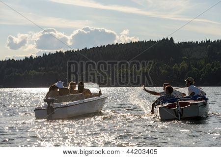 Silhouette of group of friends racing with powerboats on lake