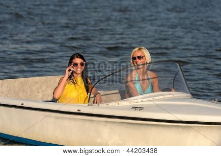 Young women in sunglasses sitting in motorboat driving