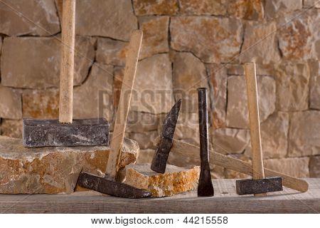 Hammer mason tools of stonecutter masonry work in a construction stone wall