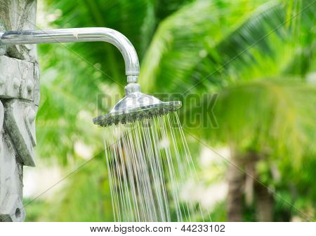 Tropical refreshing shower under palm trees