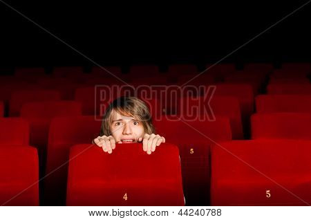 young man in the cinema hiding behind a chair