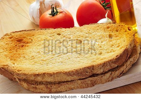 toasted bread slices, and garlic, olive oil and tomato, to prepare pa amb tomaquet typical of Catalonia, Spain