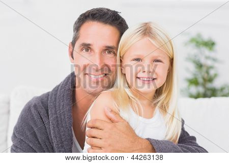 Father hugging his daughter and looking at camera