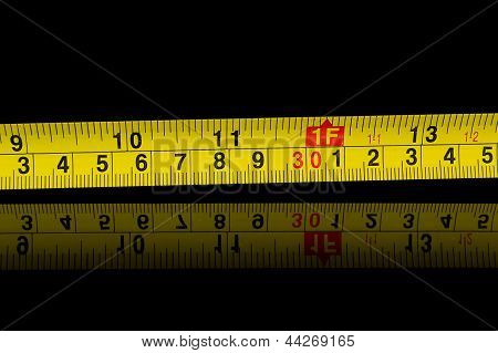 Tape measure in millimetres and inches on black
