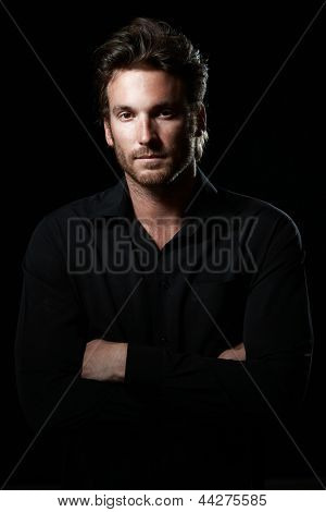 Portrait of determined goodlooking man wearing black shirt, black background.