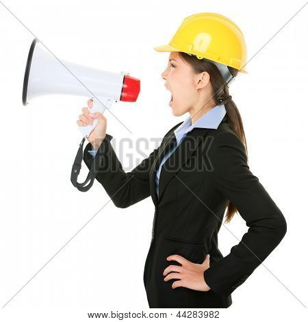 Megaphone screaming engineer contractor business woman with hard hat yelling angry, mad and upset in profile. Funny image of multicultural young professional isolated on white background in studio.