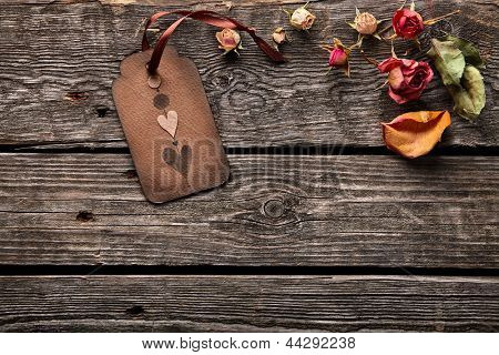 Abstract holiday background with vintage gift tag, rose petals and rose flower. On wood background.