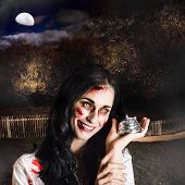 image of gruesome  - Creepy deceased zombie woman holding silver service bell in a spooky graveyard location in a depiction of death services - JPG