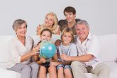 Family portrait looking at camera with a globe in sitting room