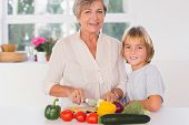 Grandmother cutting vegetables with her grandson in kitchen