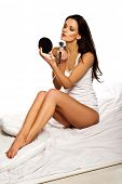 Beautiful slender brunette woman applying makeup with a large cosmetics brush and a compact mirror w