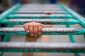 stock photo of playground school  - Hang on concept with child swinging on monkey bars - JPG