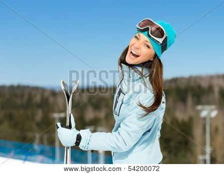 Half-length portrait of female downhill skier with skis in hands. Concept of winter sports and cute entertainment
