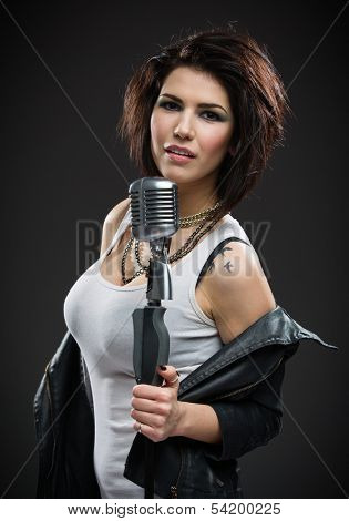 Half-length portrait of female rock musician wearing black jacket and keeping microphone on grey background. Concept of music and rave