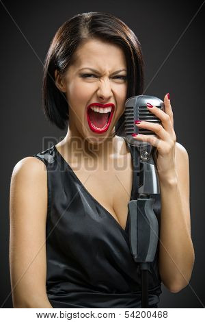 Half-length portrait of shouting female musician wearing black evening dress and keeping microphone on grey background. Concept of music and retro fashion
