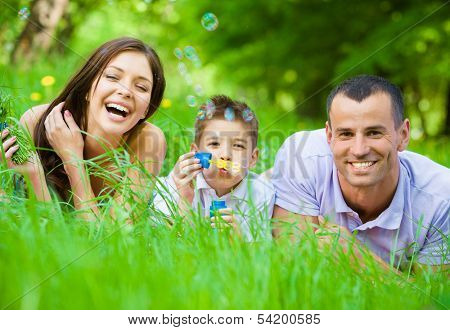 Happy family of three lying on grass while son blows bubbles. Concept of happy family relations and carefree leisure time