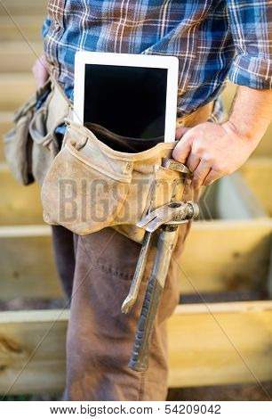 Midsection of manual worker with tablet computer and hammer in toolbelt at site