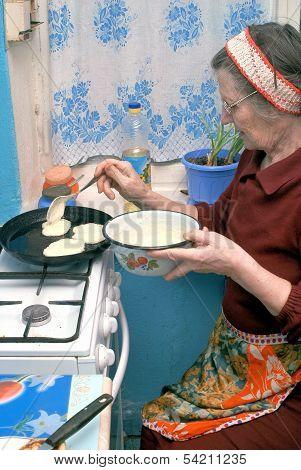 An elderly woman fry pancakes