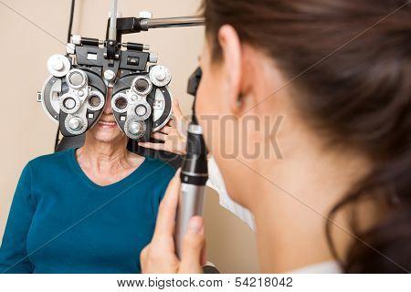 Optometrist examining eyes of senior woman with a phoropter