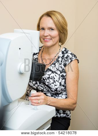 Optometrist examining patient's eye in clinic with digital retina camera