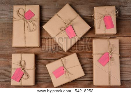 Six holiday packages wrapped in brown kraft paper and tied with twine. The parcels are all different sizes and shapes and resting on a rustic wooden table. A blank gift tag attached to each gift.