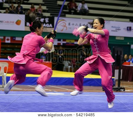 KUALA LUMPUR - NOV 05: Members of Australia's dalian team performs a fight scene in the Women's Dual Event at the 12th World Wushu Championship on November 05, 2013 in Kuala Lumpur, Malaysia.