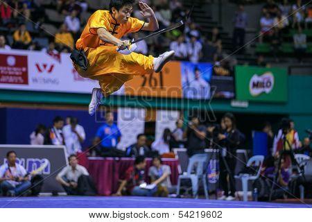 KUALA LUMPUR - NOV 03: Brazil's Henry Yuji Nakata executes a high kick in the Men's 'Daoshu' Event at the 12th World Wushu Championship on November 03, 2013 in Kuala Lumpur, Malaysia.