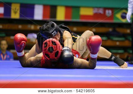KUALA LUMPUR - NOV 05: China's Zhang Kaiyin (black) takes down Egypt's Ahmed Ebrahim in the Sanda boxing event, 12th World Wushu Championship on November 05, 2013 in Kuala Lumpur, Malaysia.