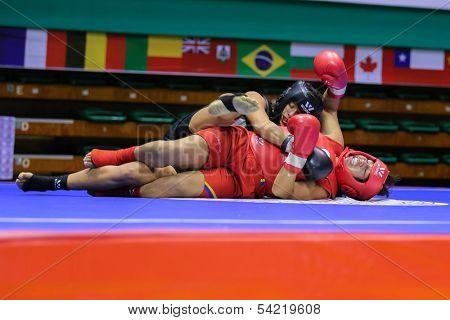 KUALA LUMPUR - NOV 03: Equador's Maria Quispe (red) downs Italy's Antonia Di Biase in the Women's 'Sanda' event of the 12th World Wushu Championship on November 03, 2013 in Kuala Lumpur, Malaysia.