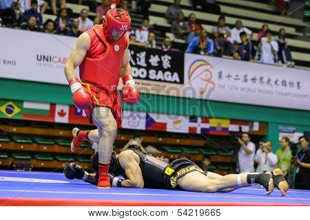KUALA LUMPUR - NOV 05: Russia's Salikhov Muslim (red) knocks down Iran's Amir Fazli in the Sanda boxing event, 12th World Wushu Championship on November 05, 2013 in Kuala Lumpur, Malaysia.