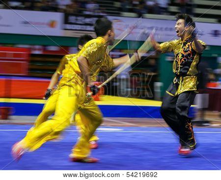 KUALA LUMPUR - NOV 05: Members of Singapore's dalian team performs a fight scene in the Men's Dual Event at the 12th World Wushu Championship on November 05, 2013 in Kuala Lumpur, Malaysia.