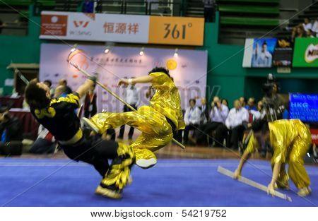 KUALA LUMPUR - NOV 05: Hong Kong's dalian team performs a fight scene in the Men's Dual Event at the 12th World Wushu Championship on November 05, 2013 in Kuala Lumpur, Malaysia.