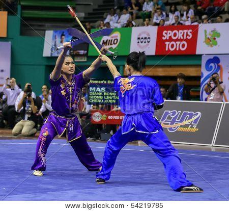 KUALA LUMPUR - NOV 05: Members of the Malaysian dalian team performs a fight scene in the Women's Dual Event at the 12th World Wushu Championship on November 05, 2013 in Kuala Lumpur, Malaysia.