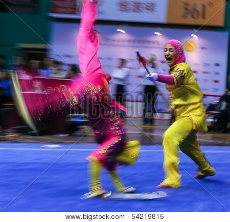 KUALA LUMPUR - NOV 05: Members of the Iranian dalian team performs a fight scene in the Women's Dual Event at the 12th World Wushu Championship on November 05, 2013 in Kuala Lumpur, Malaysia.
