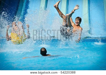 Young People Having Fun On Water Slides In Aqua Park