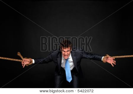 Businessman Being Pulled By Rope On Both Sides.
