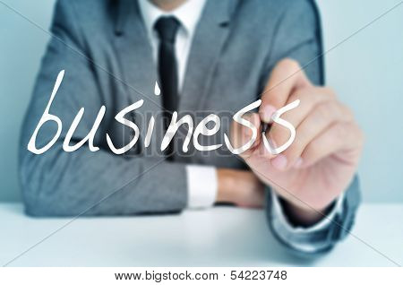 man wearing a suit sitting in a table writing the word business in the foreground
