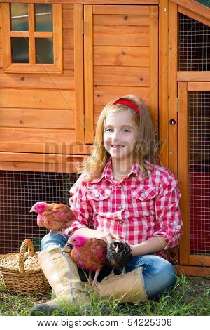 breeder hens kid girl rancher blond farmer playing with chicks in chicken tractor coop