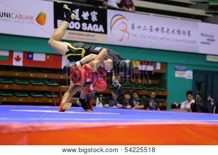 KUALA LUMPUR - NOV 03: Tunisia's Achraf Hadad (red) fights Romania's Rus Traian in the Men's 'Sanda' event of the 12th World Wushu Championship on November 03, 2013 in Kuala Lumpur, Malaysia.