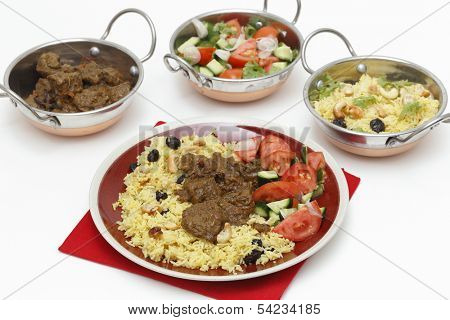 Beef madras curry served with saffron, raisin and roast cashew nut pilau rice and a salad of tomato, cucumber and shallots. Kadai serving bowls with each of the elements are at the back.