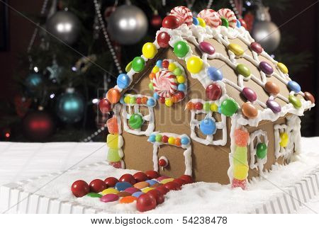 Beautiful Christmas Table Setting In Front Of Christmas Tree, Featuring A Gingerbread House Made Wit